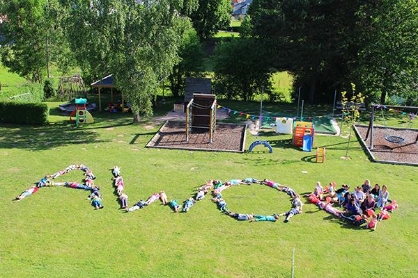 Kinder bilden auf dem Rasen den Schriftzug AWO